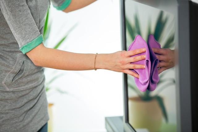 自宅の洗剤でテレビを掃除する女性