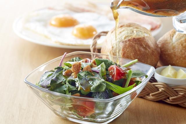 サラダにドレッシングをかける、目玉焼きとパン