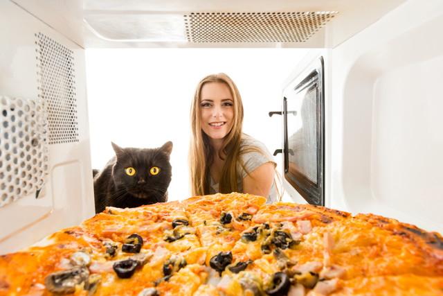 電子レンジで見ている少女と猫