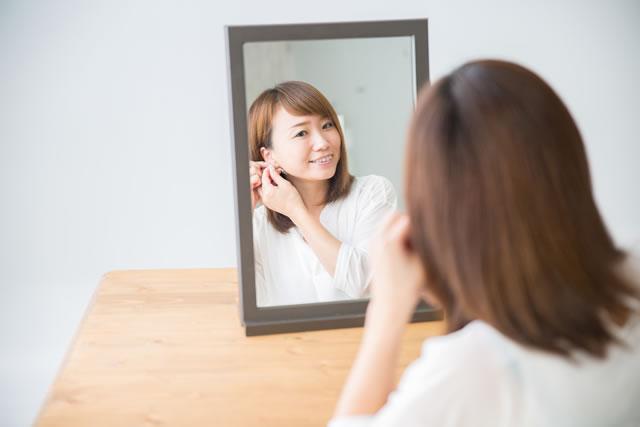 鏡をみながらピアスをつける女性