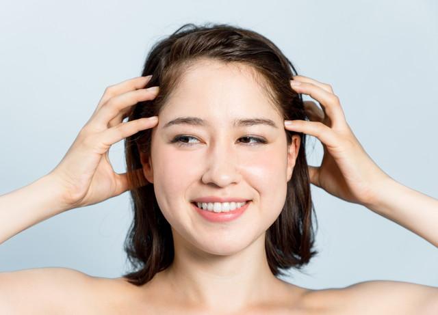 側頭部に手を当てる女性の顔のアップ