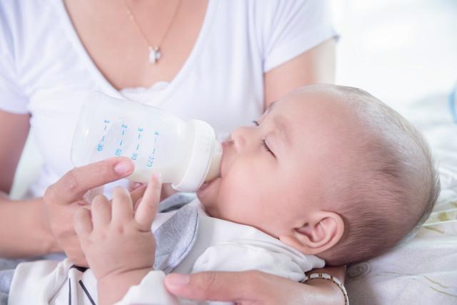 ボトルからミルクを飲む小さな子