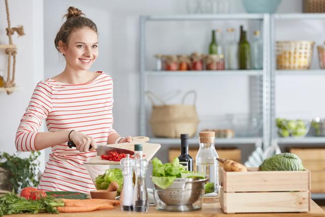 赤い食材と包丁を持つ女性、キッチンで料理