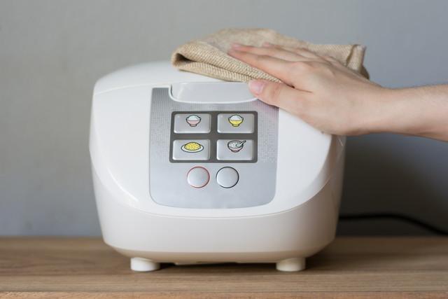 炊飯器を掃除する人