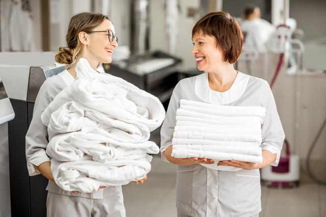 クリーニング店へ布団を持っていく女性