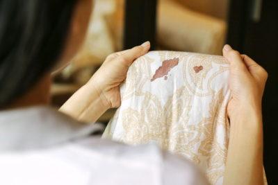 シミのついたシーツを見る女性