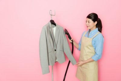 スーツのホコリを落としている女性