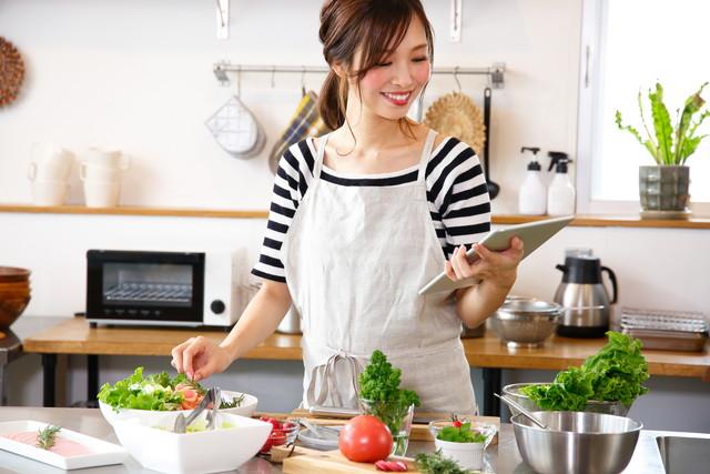 サラダを作りながらレシピを確認する女性