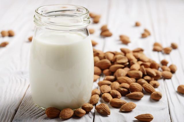 アーモンドと白い木製のテーブルに石工の瓶に牛乳