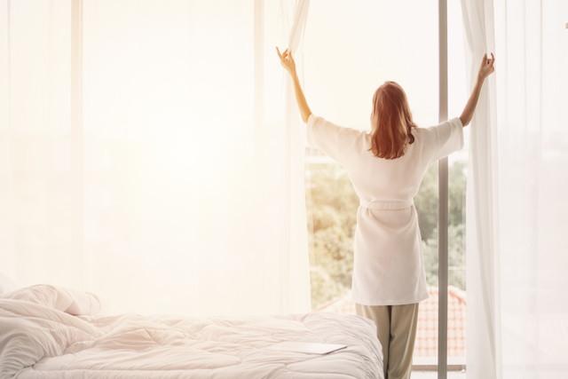 寝室でカーテンを開け放つ女性