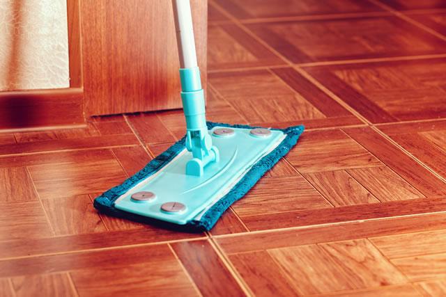 A blue floor mop stands on a tile floor.