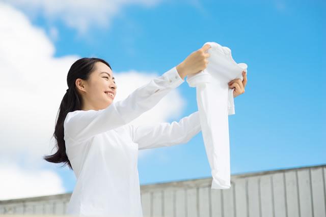 真っ白な洗濯物と女性