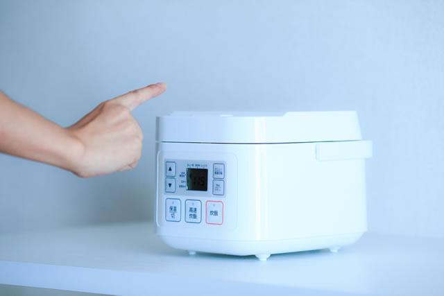 炊飯器のボタンを押す