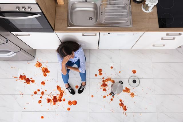 床の汚れに落ち込む女性
