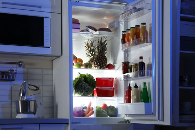 Open refrigerator full of products in stylish kitchen interi