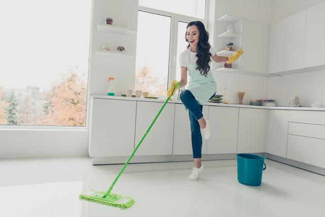 楽しそうに床掃除をする女性