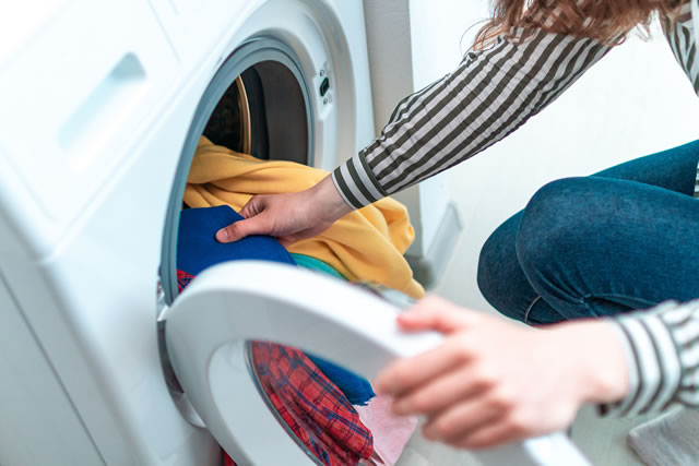 洗濯物を電気洗濯機に入れている様子
