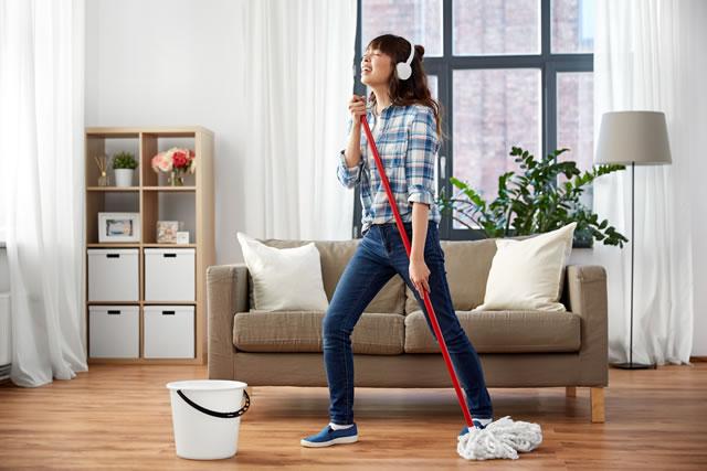 楽しみながら掃除をする女性