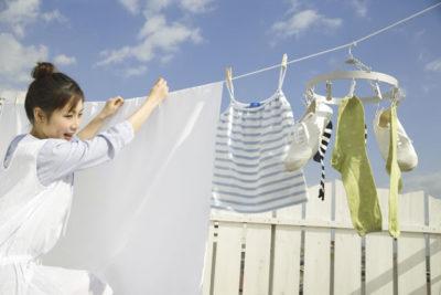 靴と洗濯物を干す女性