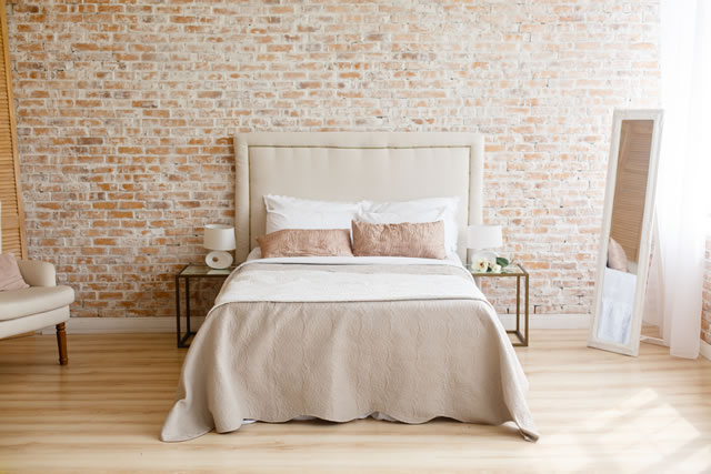 A room in light loft stile with brick wall and light furniture. Comfortable bedroom. A combination of modern and old. Join the glass and brick. Modern lamp on a glass bedside table.