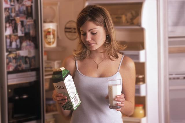 牛乳パックを手に取る女性