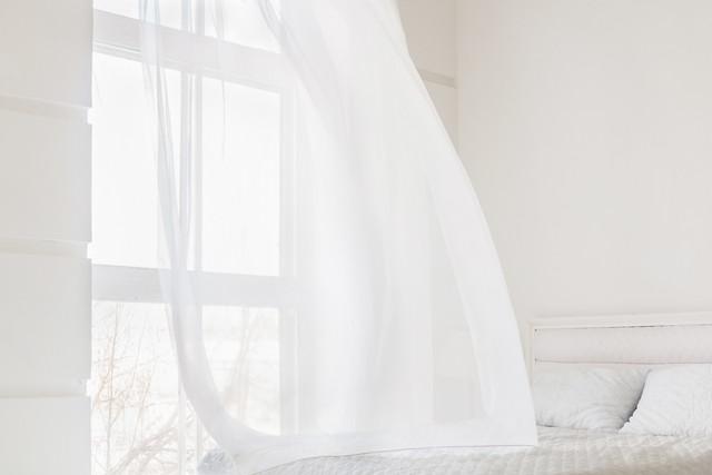 真っ白な空間、窓から風が入りカーテンを揺らす様子