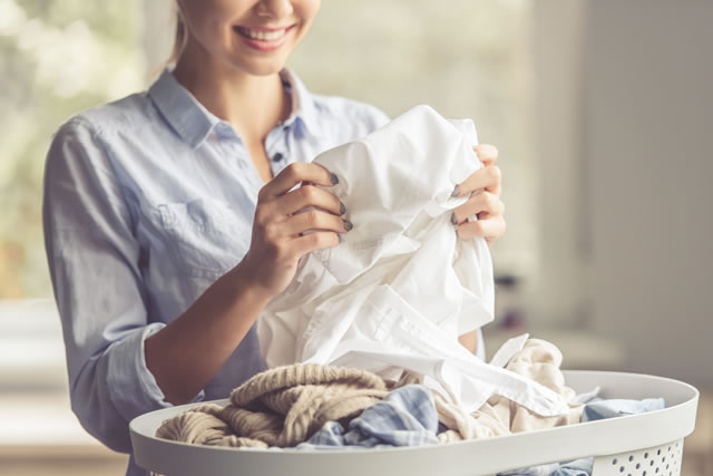 白い服を手にする女性、カゴの中に洗濯物