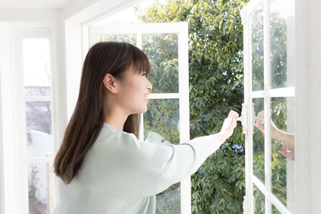 窓を開ける女性