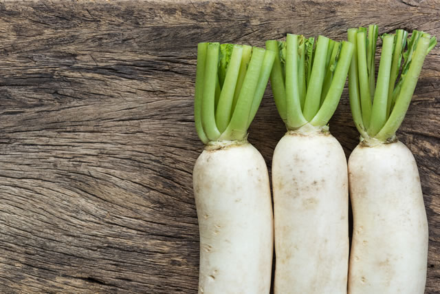 white radish on old and crack wooden surface background, top view
