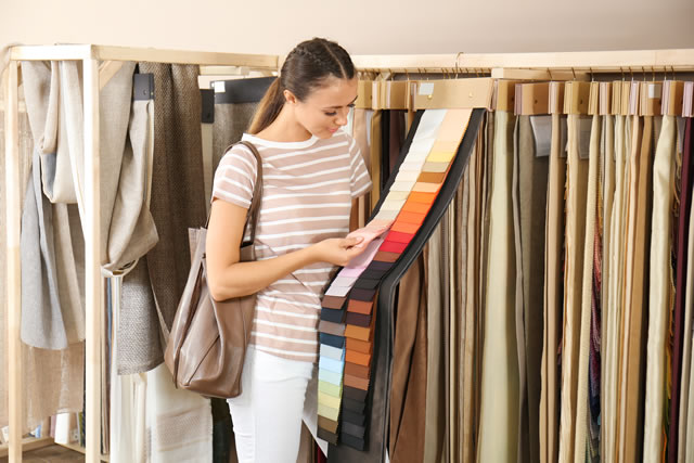 カーテンの色見本を見ている女性