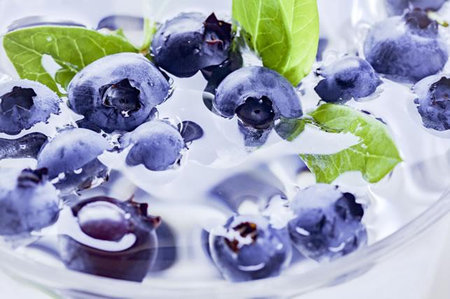 透明な容器に水とブルーベリーと葉