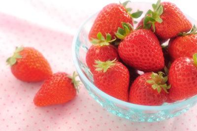 透明なガラスの容器に入ったいちご、ピンクの敷物