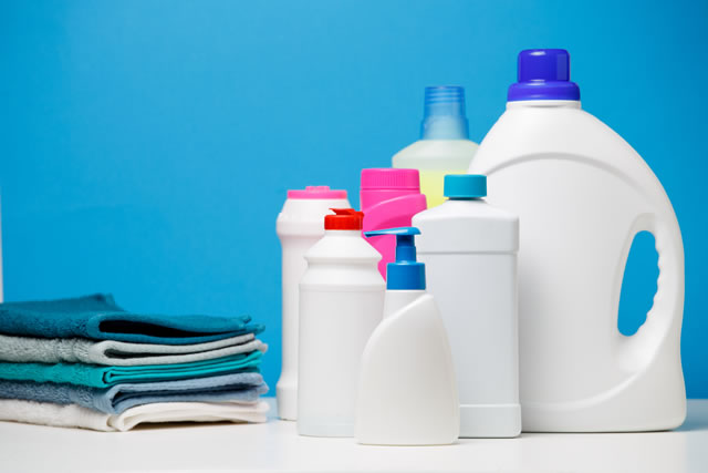 Photo of different bottles of cleaning products and colored towels isolated on blue background