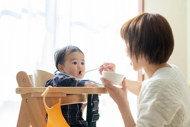 赤ちゃんに離乳食をあげているお母さん
