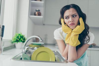 溜まった食器に嫌気が差している女性