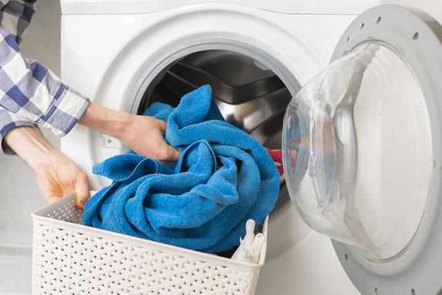 ドラム式洗濯機に青い洗濯物を入れるところ