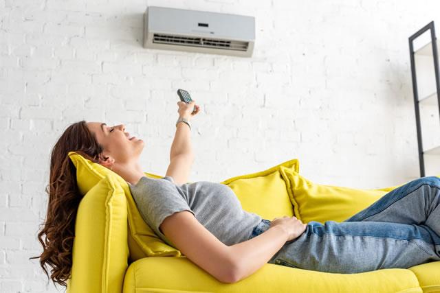 エアコンの下で寝転がっている女性
