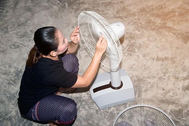 扇風機を分解する女性