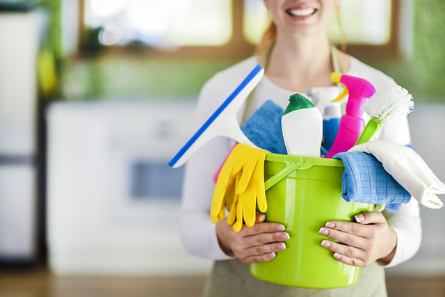 Woman holding cleaning items in plastic bucket. Kitchen serv
