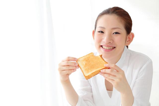 トーストを食べる笑顔の女性
