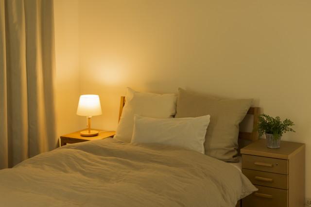 小さな明かりがついたナチュラルな寝室
