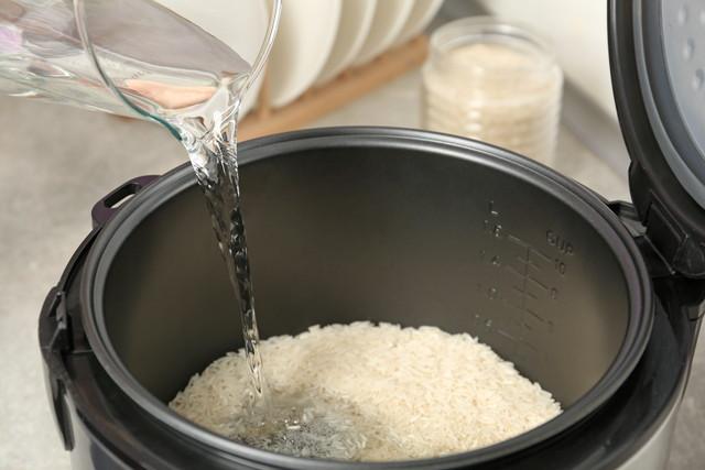 キッチンでモダンな炊飯器に注ぐ水