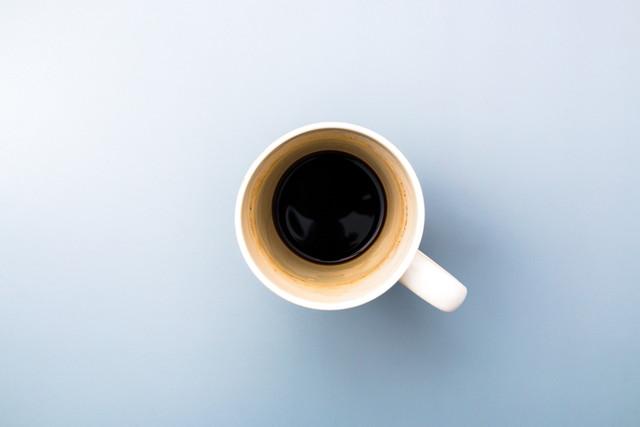 灰色の背景に空の白いコーヒーマグ