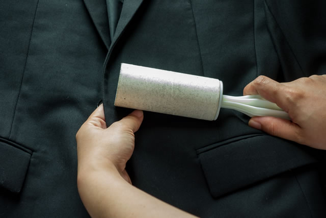 Dry cleaning and business theme: a man hand with black suit holding a white sticky brush for cleaning clothes and furniture from dust