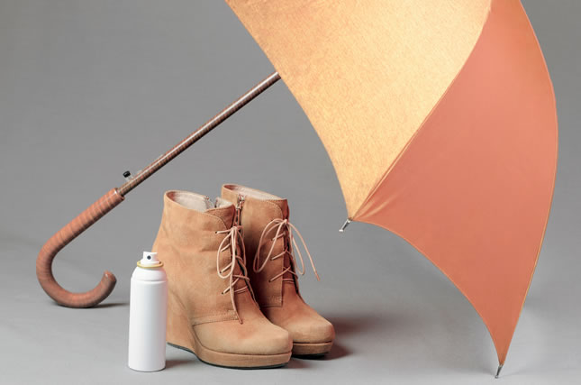 Brown suede boots under an umbrella on a gray background. Waterp