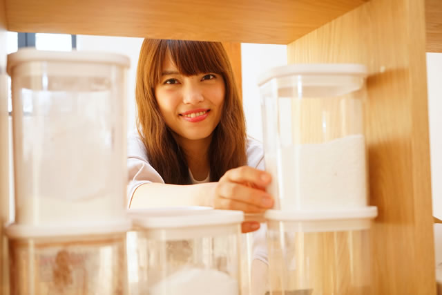Young Japanese woman looking for a kitchen tools or materials キッチンの戸棚から調味料を探す若い日本人の女性