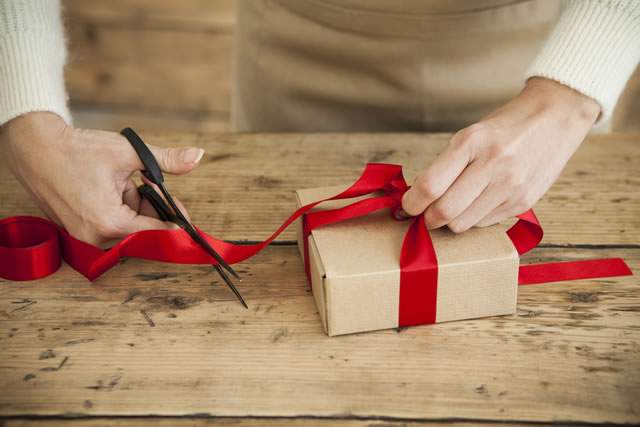 The woman is wearing a ribbon in the present box