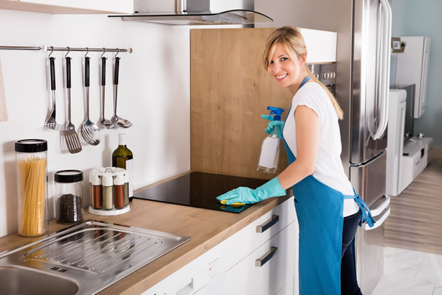Woman Cleaning Induction Stove In Kitchen