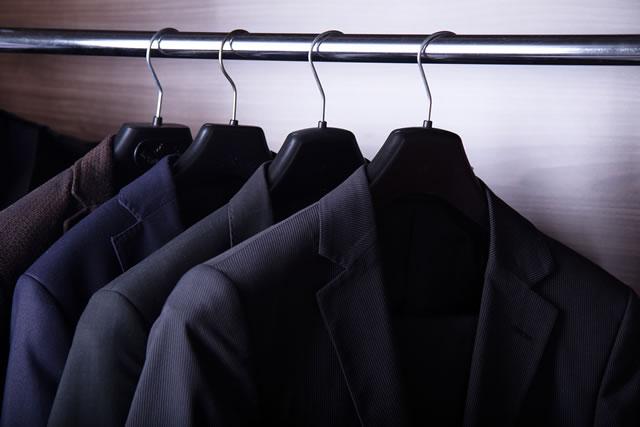 Men's suit jackets hanging in closet