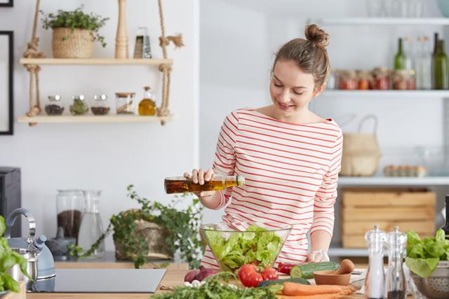 オリーブオイルをサラダにかける女性